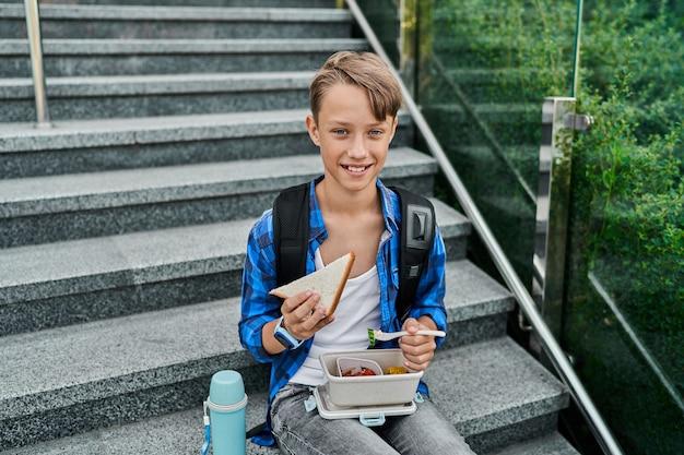 Fröhlicher kleiner schülerjunge isst auf treppen in der nähe der schule mit lunchbox und thermoskanne zu mittag.