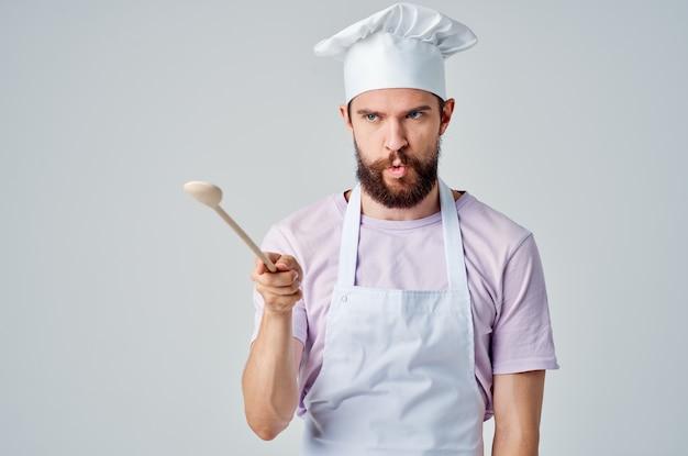 Fröhlicher koch mit einem löffel in der hand, der lebensmittelküchenrestaurantindustrie kocht