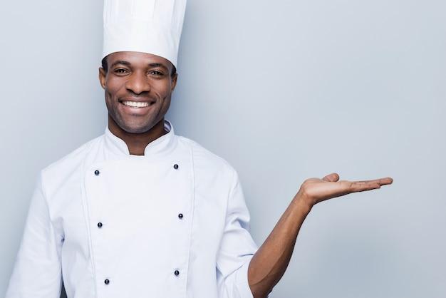 Fröhlicher koch. selbstbewusster junger afrikanischer koch in weißer uniform, der kopienraum hält und lächelt