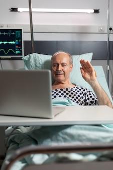 Fröhlicher kranker älterer mann, der während der videokonferenz mit einem laptop im bett auf die kamera winkt und durch einen sauerstoffschlauch atmet. mann erholt sich nach operation und behandlung.