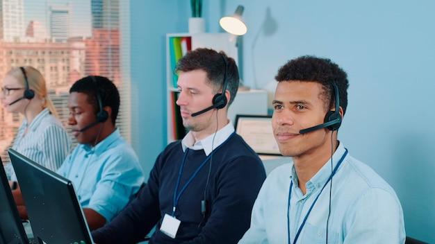 Fröhlicher kundendienstmitarbeiter gemischter ethnischer zugehörigkeit, der mit einem headset telefoniert, das er in mod...