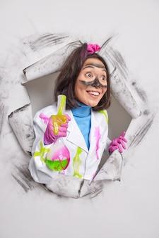 Fröhlicher laborassistent mit schmutzigem gesicht hält medizinische studien hält flasche mit chemischer flüssigkeit sieht glücklich beiseite, gekleidet in uniform bricht durch papier