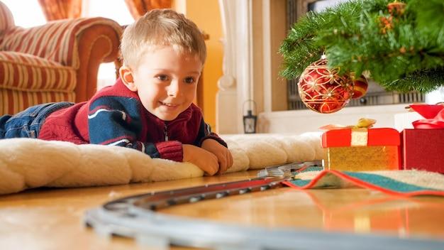 Fröhlicher lachender kleinkindjunge, der auf dem boden liegt und auf spielzeugeisenbahn um den großen weihnachtsbaum schaut