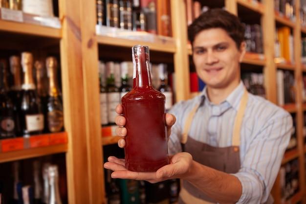 Fröhlicher ladenbesitzer, der lächelnd flasche zur kamera heraushält, raum kopiert