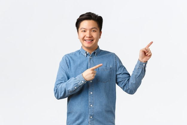 Fröhlicher lächelnder asiatischer junger mann mit hosenträgern im blauen hemd, der mit den fingern in der oberen rechten ecke stolz und selbstbewusst zeigt, einen link zeigt oder eine ankündigung macht, weißer hintergrund steht