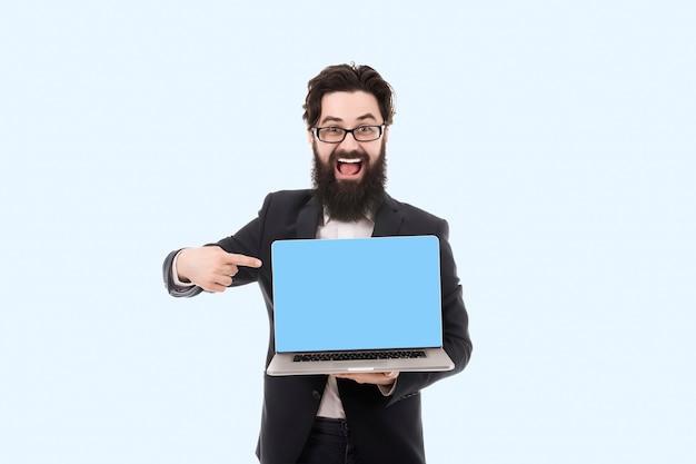 Fröhlicher lächelnder bärtiger geschäftsmann, der auf leeren laptop-computerbildschirm zeigt