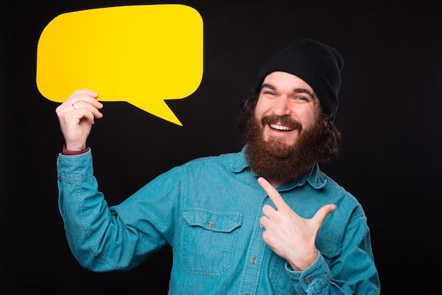 Fröhlicher lächelnder bärtiger hipster-mann, der auf leere sprechblase zeigt