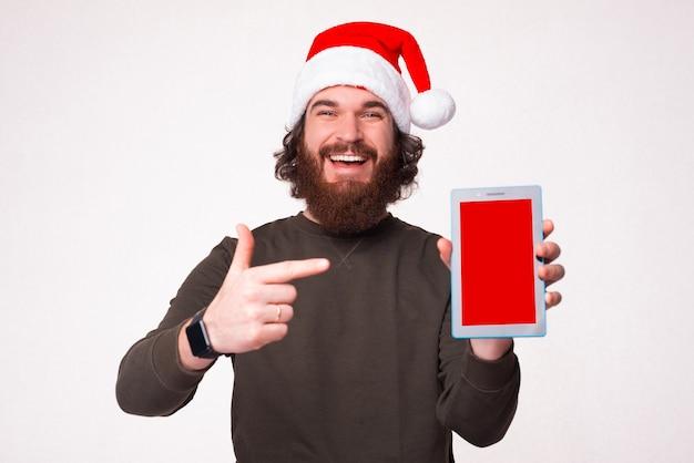 Fröhlicher lächelnder bärtiger hipster-mann mit weihnachtsmann-hut, der auf den leeren bildschirm auf dem tablet zeigt