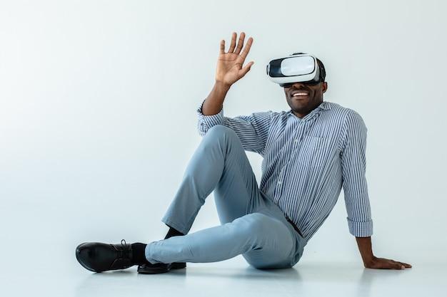 Fröhlicher lächelnder erwachsener afroamerikanischer mann, der auf dem boden sitzt, während vr-gadget verwendet wird