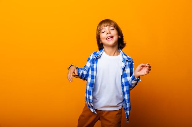 Fröhlicher lächelnder kleiner junge, der an der gelben wand springt und spaß hat. schulkonzept.