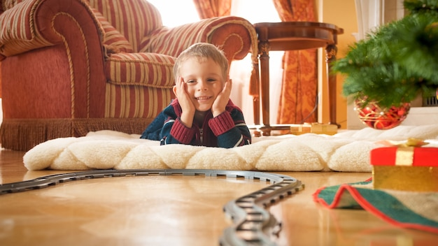 Fröhlicher lächelnder kleiner junge, der auf der kreiseisenbahn unter dem weihnachtsbaum im wohnzimmer des hauses schaut. kind, das an neujahr oder weihnachten geschenke und spielzeug erhält