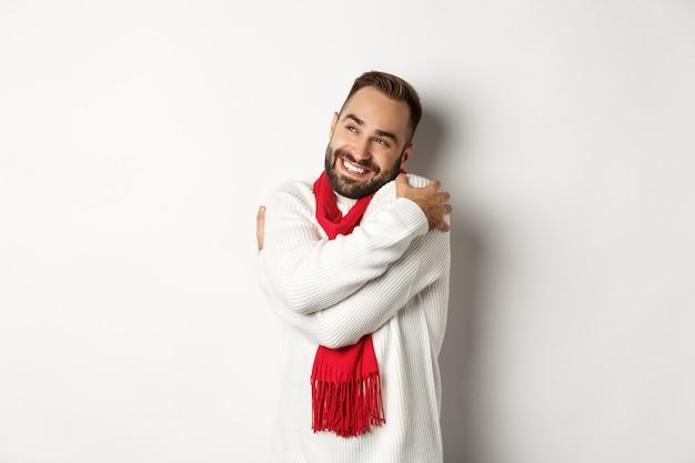Fröhlicher lächelnder mann, der sich selbst umarmt und in der oberen linken ecke zufrieden aussieht, einen warmen und bequemen winterpullover trägt und auf weißem hintergrund steht.