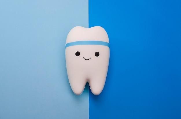Fröhlicher lächelnder zahn auf einem blau