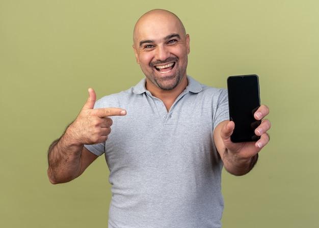 Fröhlicher, lässiger mann mittleren alters, der ein mobiltelefon zeigt, das isoliert auf einer olivgrünen wand darauf zeigt?