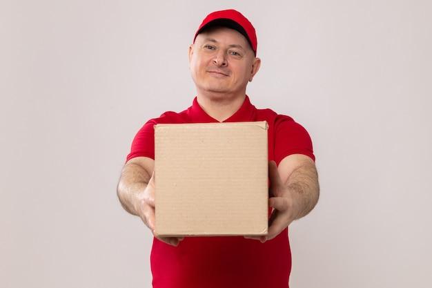 Fröhlicher liefermann in roter uniform und mütze mit karton mit blick in die kamera lächelnd freundlich auf weißem hintergrund stehend