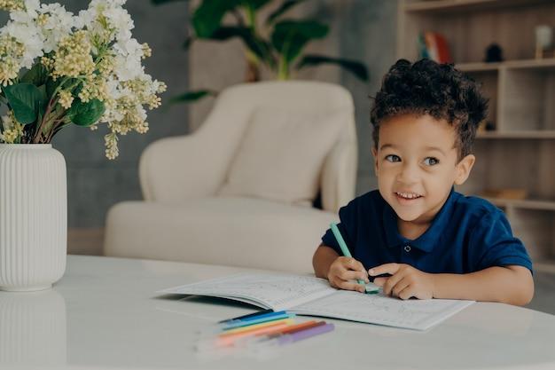 Fröhlicher, lockiger mischling, der tiere im malbuch mit filzstiften färbt, beiseite schaut und lächelt, während er im gemütlichen wohnzimmer zu hause vor dem tisch sitzt. freizeitaktivitäten für kinder