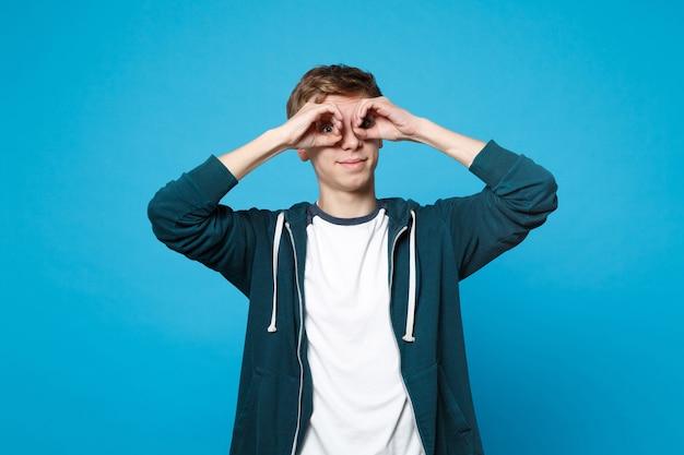 Fröhlicher lustiger junger mann in freizeitkleidung mit händen in der nähe der augen, imitieren von brillen oder ferngläsern einzeln auf blauer wand. menschen aufrichtige emotionen, lifestyle-konzept.