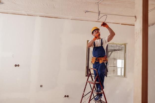 Fröhlicher männlicher arbeiter, der elektrokabel an der decke befestigt