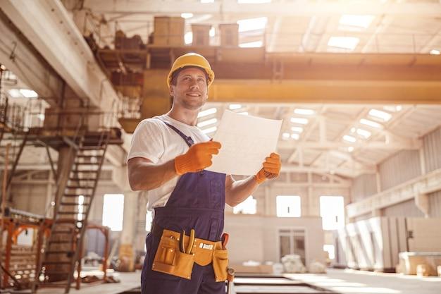Fröhlicher männlicher arbeiter, der gebäudearchitekturplan hält