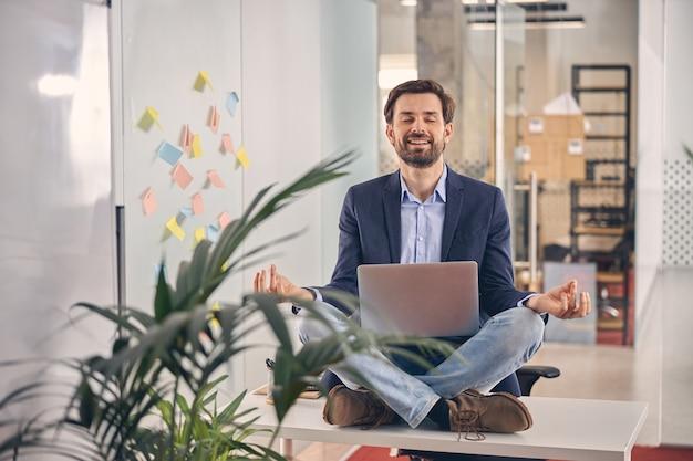 Fröhlicher männlicher arbeiter, der im lotussitz sitzt und lächelt, während er meditations-yoga-übungen im büro praktiziert