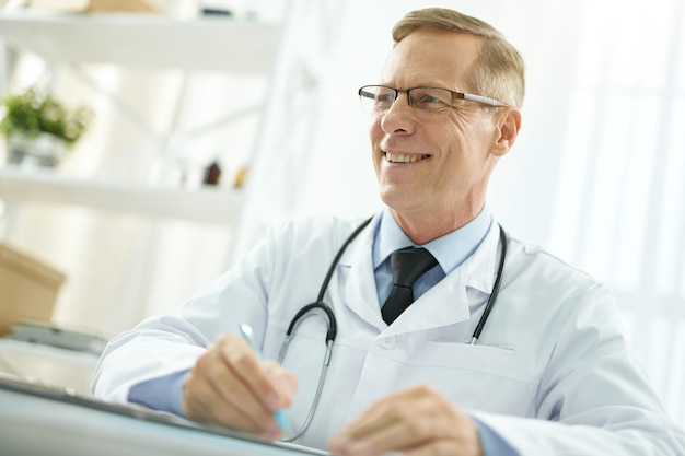Fröhlicher männlicher arzt im laborkittel, der in der klinik arbeitet