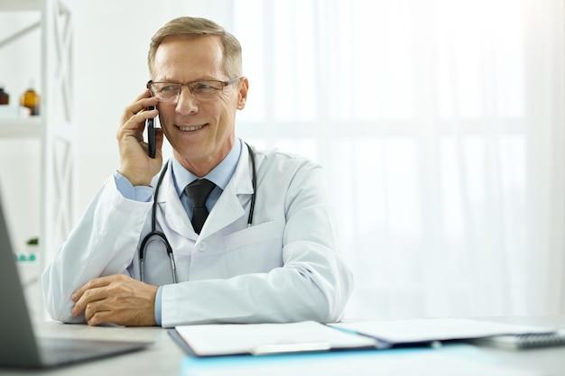 Fröhlicher männlicher arzt mit telefongespräch in der klinik