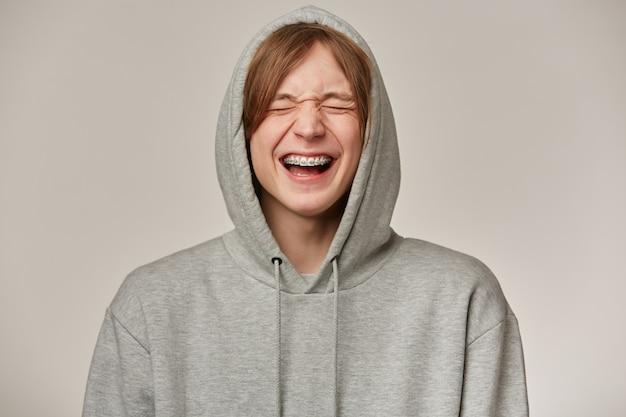 Fröhlicher männlicher, gutaussehender mann mit blonden haaren. grauen hoodie tragen. hat zahnspangen. menschen- und emotionskonzept. setzt die kapuze auf und lacht mit geschlossenen augen. stehen sie isoliert über grauer wand