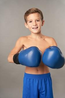 Fröhlicher männlicher kinderboxer, der boxhandschuhe und shorts trägt, während er in die kamera schaut und lächelt