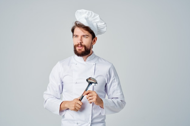 Fröhlicher männlicher koch mit einem topf in den händen, der lebensmittelküchengeräte zubereitet