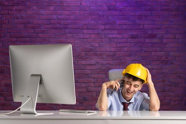 Fröhlicher männlicher konstrukteur der vorderansicht hinter dem schreibtisch, der am telefon spricht