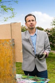 Fröhlicher männlicher maler, der während eines kunstunterrichts an einem bock- und staffelei-gemälde mit öl und acryl arbeitet