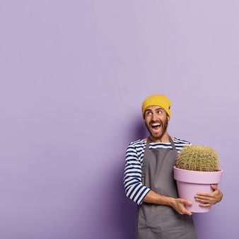 Fröhlicher männlicher pflanzenliebhaber hält topfkaktus, kümmert sich zu hause um zimmerpflanzen