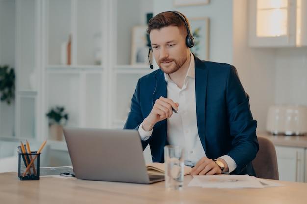Fröhlicher männlicher unternehmensberater im headset, der zu hause arbeitet, während er während eines online-meetings oder eines videoanrufs auf dem laptop mit einem partner oder kunden spricht und an seinem arbeitsplatz sitzt. onlinegeschäft