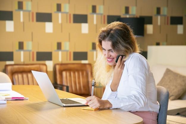 Fröhlicher manager, der das projekt mit dem kunden am telefon bespricht