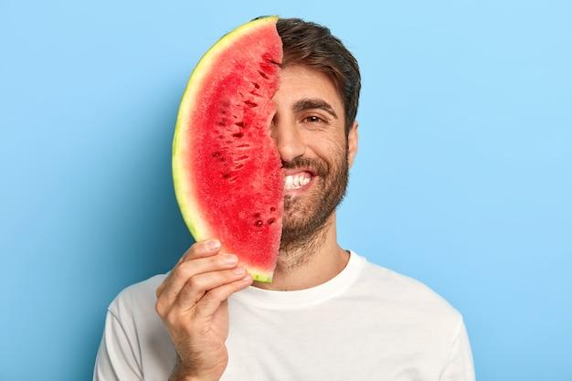 Fröhlicher mann an einem sommertag, der eine scheibe wassermelone hält