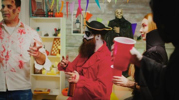 Fröhlicher mann auf der halloween-party verkleidet wie ein pirat mit seinen monsterfreunden, die tanzen und spaß haben.