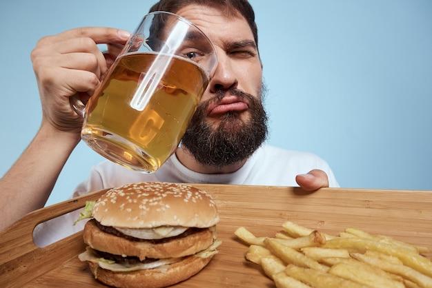 Fröhlicher mann bierkrug hamburger pommes frites fast-food-diät