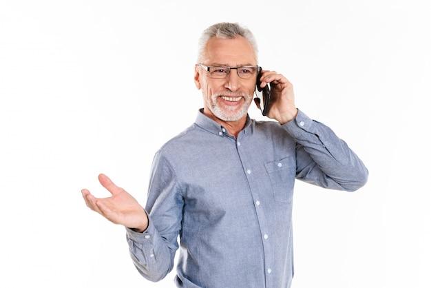 Fröhlicher mann, der auf smartphone lokalisiert über weiß spricht
