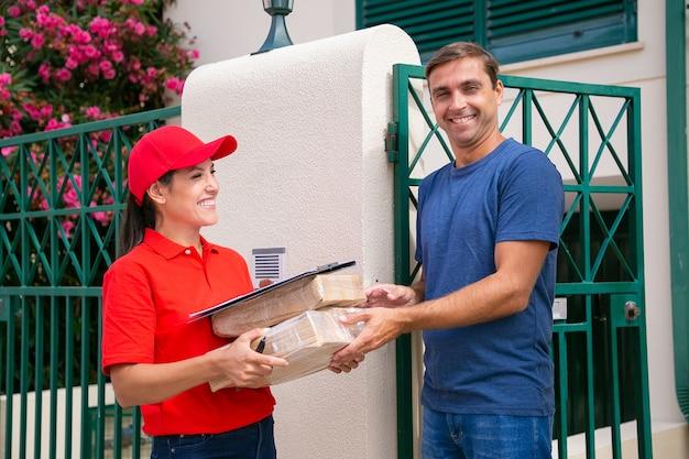 Fröhlicher mann, der bestellformular-lieferfrau in roter uniform erhält. glücklicher brünetter weiblicher kurier in der kappe, die pakete liefert und draußen steht. express-lieferservice und online-shopping-konzept