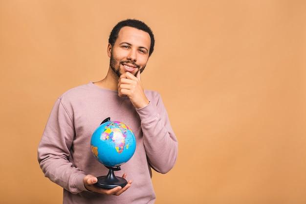 Fröhlicher mann, der den globus mit liebe und sorgfalt lokalisiert über beige hält