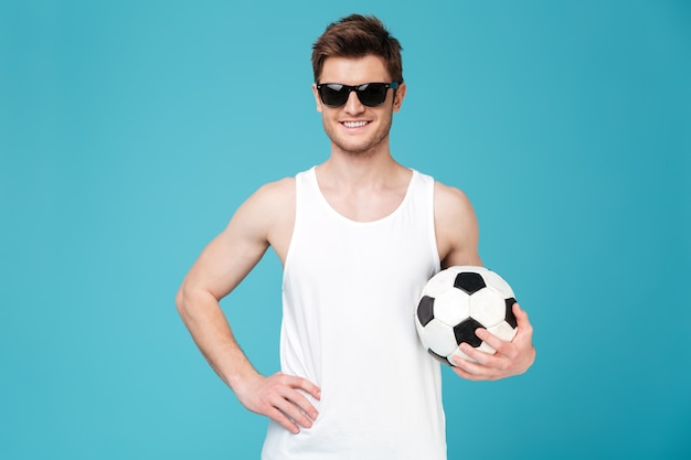 Fröhlicher mann, der fußball hält