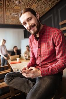 Fröhlicher mann, der im büro sitzt und telefon benutzt