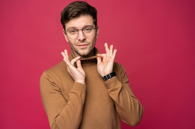 Fröhlicher mann, der lacht und direkt schaut. porträt eines glücklichen jungen mannes, der über rosa hintergrund steht.