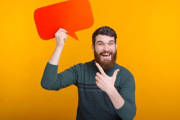 Fröhlicher mann, der über gelbe wand steht und auf sprechblase zeigt