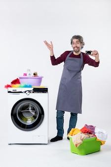 Fröhlicher mann der vorderansicht, der die karte hochhält, die in der nähe der waschmaschine auf weißem hintergrund steht