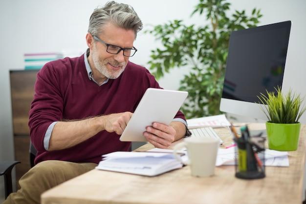 Fröhlicher mann, der websites auf seinem digitalen tablett durchsucht