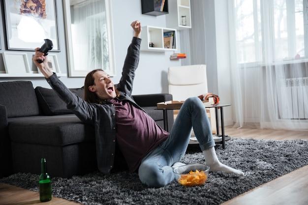 Fröhlicher mann, der zuhause drinnen sitzt, spielt mit joystick