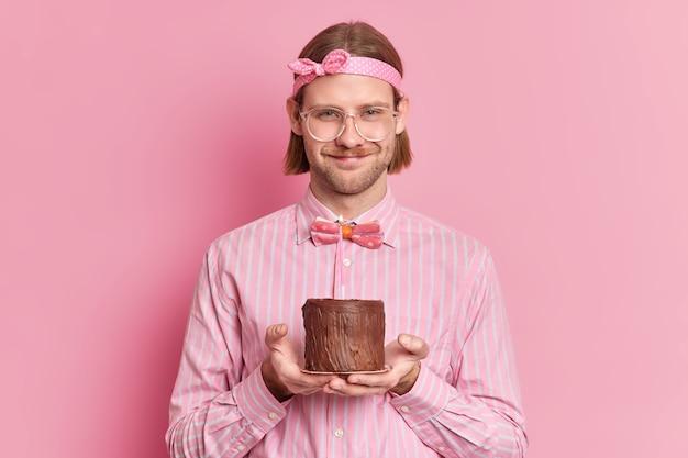 Fröhlicher mann feiert jubiläum am arbeitsplatz erhält glückwünsche von kollegen hält kleinen kuchen mit brennender kerze trägt große brille und festliche kleidung