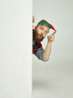 Fröhlicher mann im elfenkostüm, der etwas mit seinem finger zeigt
