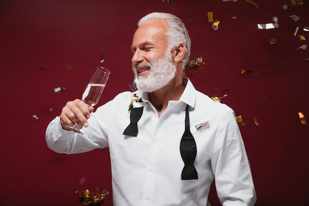 Fröhlicher mann im klassischen outfit trinkt champagner